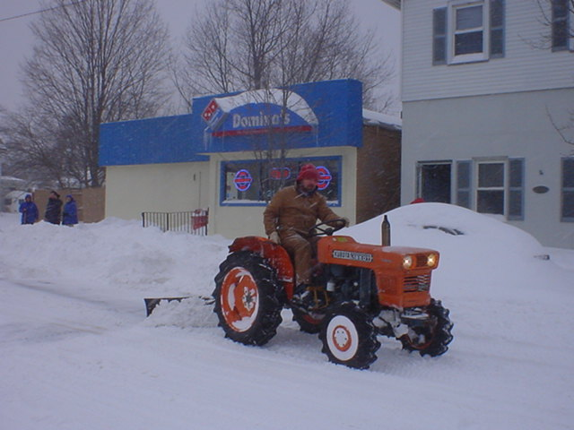 An unidentified Borough Worker Clears Snow from Around Domino's Pizza.