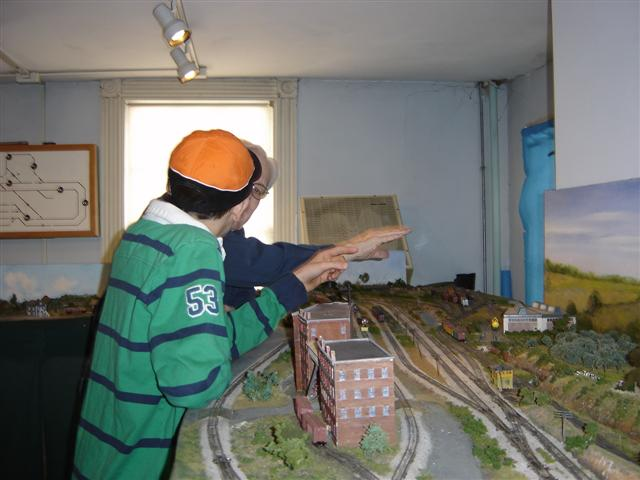 Chuck Bindig discusses the model railroad room with a young boy.